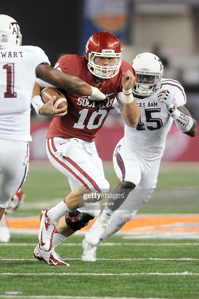 Quarterback Blake Bell #11 of the Oklahoma Sooners runs for a first down past linebacker Steven Jenkins #45 of the Texas A&M Aggies on January 4, 2012 at the Cotton Bowl at Cowboys Stadium in Arlington, Texas.