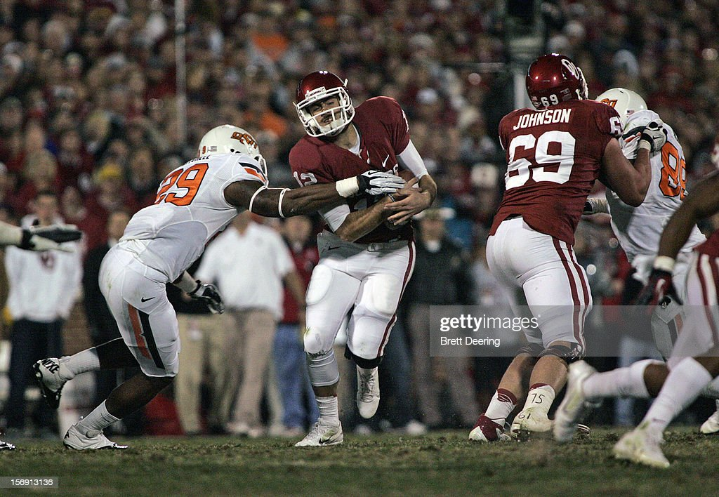 Quarterback Blake Bell #10 of the Oklahoma Sooners tries to shake a tackle by linebacker Joe Mitchell #29 of the Oklahoma State Cowboys November 24, 2012 at Gaylord Family-Oklahoma Memorial Stadium in Norman, Oklahoma. Oklahoma defeated Oklahoma State 51-48 in overtime.