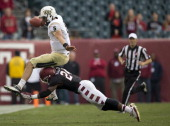 Quarterback Blake Bortels of the University of Central Florida Knights jumps over the tackle of cornerback Jihaad Pretlow of the Temple University...