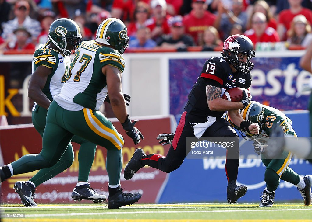 Quarterback Bo Levi Mitchell #19 of the Calgary Stampeders is tackled by Marcell Young #23 of the Edmonton Eskimos in the second half of their CFL football game September 1, 2014 at McMahon Stadium in Calgary, Alberta, Canada.