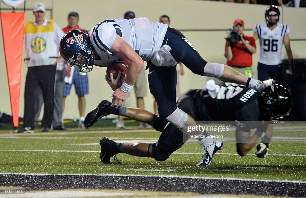 Quarterback Bo Wallace #14 of the Ole Miss Rebels dives over Andrew Williamson #32 of the Vanderbilt Commodores to score a touchdown at Vanderbilt Stadium on August 29, 2013 in Nashville, Tennessee.