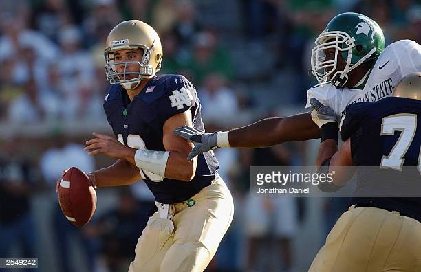 Quarterback Brady Quinn of Notre Dame avoids pressure from end Clifton Ryan of Michigan State while looking for a receiver during a game on September...