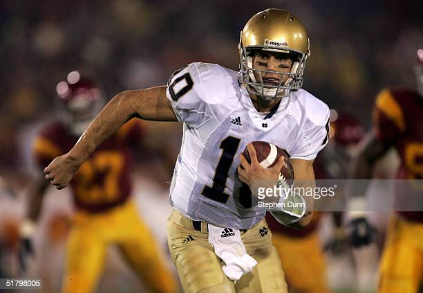 Quarterback Brady Quinn of the Notre Dame Fighting Irish carries the ball against the USC Trojans on November 27 2004 at the Los Angeles Coliseum in...