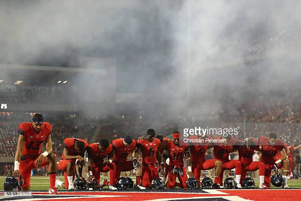 Quarterback Brandon Dawkins of the Arizona Wildcats kneels with teammates before the start of the college football game against the Stanford Cardinal...