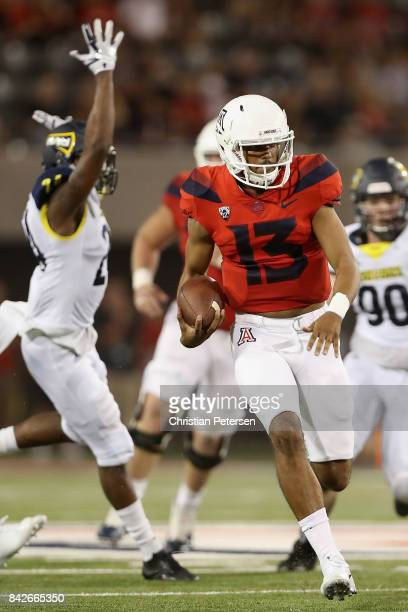 Quarterback Brandon Dawkins of the Arizona Wildcats scrambles with the football during the second half of the college football game against the...