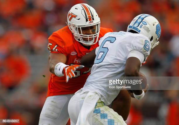 UNC quarterback Brandon Harris attempts to elude Virginia Tech linebacker Andrew Motuapuaka in the backfield during a college football game between...