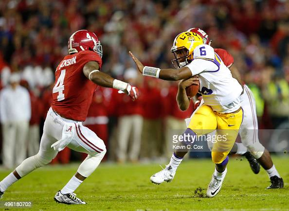 Quarterback Brandon Harris of the LSU Tigers rushes against Eddie Jackson of the Alabama Crimson Tide during the second quarter at BryantDenny...
