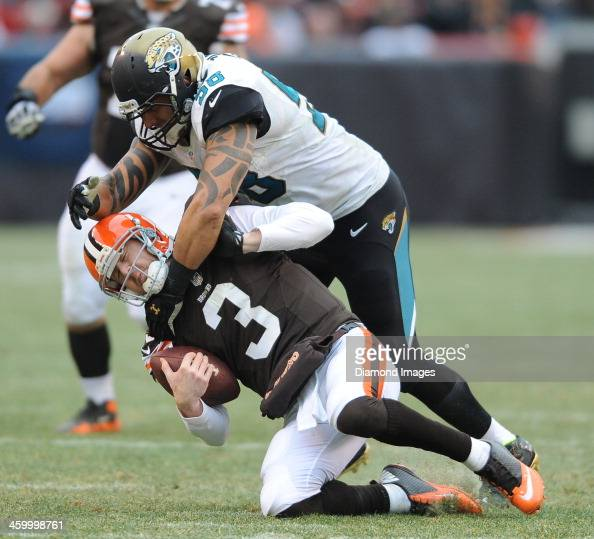 Quarterback Brandon Weeden of the Cleveland Browns is tackled by defensive end Jason Babin of the Jacksonville Jaguars during a game against the...