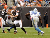 Quarterback Brandon Weeden of the Cleveland Browns rollsout to pass while being pursued by defensive tackle Nick Fairley of the Detroit Lions during...