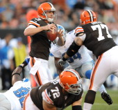 Quarterback Brandon Weeden of the Cleveland Browns steps up in the pocket to avoid contact from defensive linemen Nick Fairley and Ezekiel Ansah of...