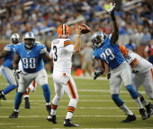 Quarterback Brandon Weeden of the Cleveland Browns tried to avoid the pass rush from defensive linemen Willie Young and Nick Fairley during a game...