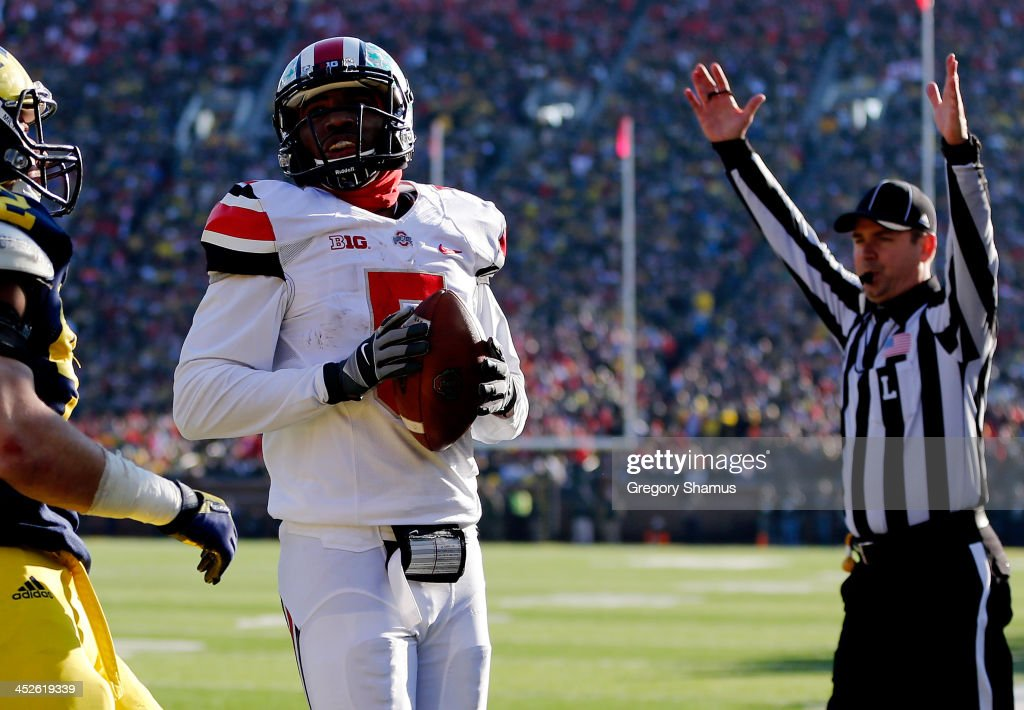 Quarterback <a gi-track='captionPersonalityLinkClicked' href=/galleries/search?phrase=Braxton+Miller&family=editorial&specificpeople=7122480 ng-click='$event.stopPropagation()'>Braxton Miller</a> #5 of the Ohio State Buckeyes scores a touchdown in the third quarter against the Michigan Wolverines during a game at Michigan Stadium on November 30, 2013 in Ann Arbor, Michigan.