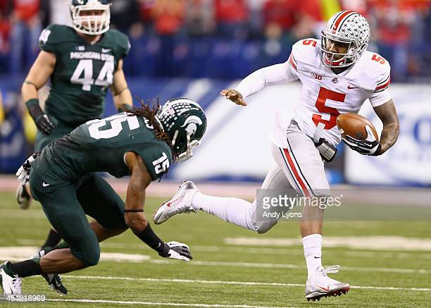 Quarterback Braxton Miller#5 of the Ohio State Buckeyes runs against the defense of Trae Waynes of the Michigan State Spartans during the Big Ten...