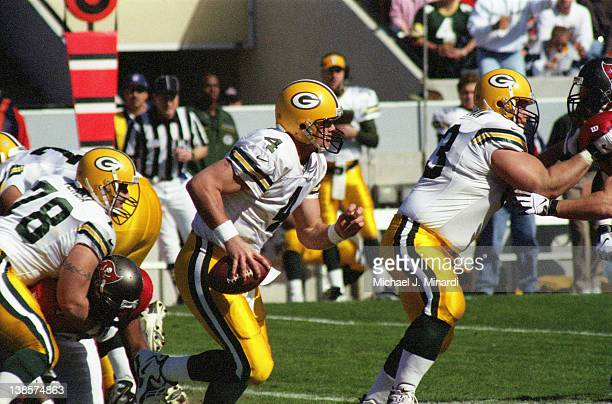 Quarterback Brett Favre of the Green Bay Packers scrambles out of the pocket following the blocking of teammate Offensive Lineman Adam Timmerman with...