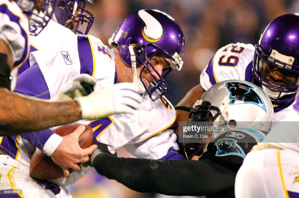 Quarterback Brett Favre of the Minnesota Vikings escapes a sack by Julius Peppers of the Carolina Panthers at Bank of America Stadium on December 20...