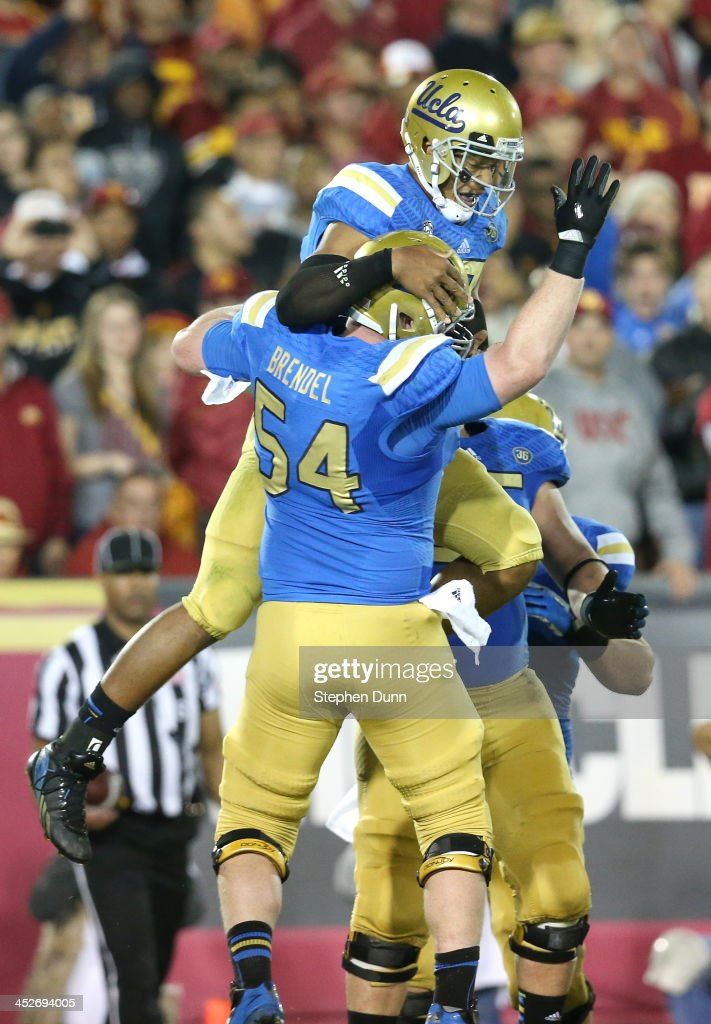 Quarterback <a gi-track='captionPersonalityLinkClicked' href=/galleries/search?phrase=Brett+Hundley&family=editorial&specificpeople=8674236 ng-click='$event.stopPropagation()'>Brett Hundley</a> #17 of the UCLA Bruins celebrates with center Jake Brendel #54 after scoring on a five yard touchdown carry in the third quarter against the USC Trojans at Los Angeles Coliseum on November 30, 2013 in Los Angeles, California. The Bruins won 35-14.