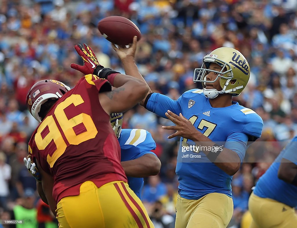 Quarterback <a gi-track='captionPersonalityLinkClicked' href=/galleries/search?phrase=Brett+Hundley&family=editorial&specificpeople=8674236 ng-click='$event.stopPropagation()'>Brett Hundley</a> #17 of the UCLA Bruins drops back to pass while defended by defensive end Wes Horton #96 of the USC Trojans in the second half at the Rose Bowl on November 17, 2012 in Pasadena, California. UCLA defeated USC