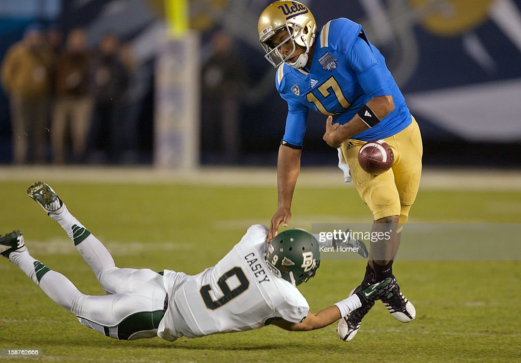 Quarterback <a gi-track='captionPersonalityLinkClicked' href=/galleries/search?phrase=Brett+Hundley&family=editorial&specificpeople=8674236 ng-click='$event.stopPropagation()'>Brett Hundley</a> #17 of the UCLA Bruins fumbles with the ball out of bounds in the first half of the game as Chance Casey #9 the Baylor Bears makes tackles in the Bridgepoint Education Holiday Bowl at Qualcomm Stadium on December 27, 2012 in San Diego, California.