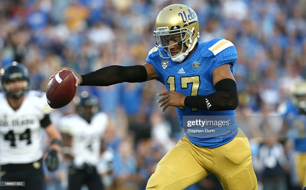 Quarterback <a gi-track='captionPersonalityLinkClicked' href=/galleries/search?phrase=Brett+Hundley&family=editorial&specificpeople=8674236 ng-click='$event.stopPropagation()'>Brett Hundley</a> #17 of the UCLA Bruins holds out the ball as he scores on an 11 yard touchdown run in the second quarter against the Colorado Buffaloes at the Rose Bowl on November 2, 2013 in Pasadena, California.