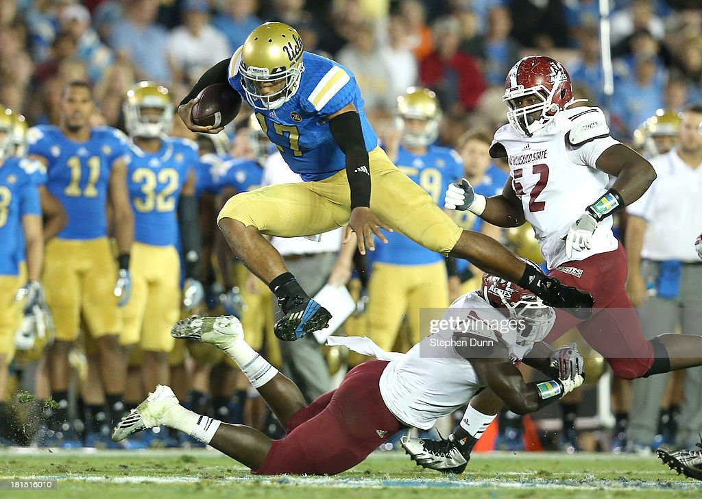 Quarterback <a gi-track='captionPersonalityLinkClicked' href=/galleries/search?phrase=Brett+Hundley&family=editorial&specificpeople=8674236 ng-click='$event.stopPropagation()'>Brett Hundley</a> #17 of the UCLA Bruins jumps over a New Mexico State Aggies defender at the Rose Bowl on September 21, 2013 in Pasadena, California. UCLA won 59-13.