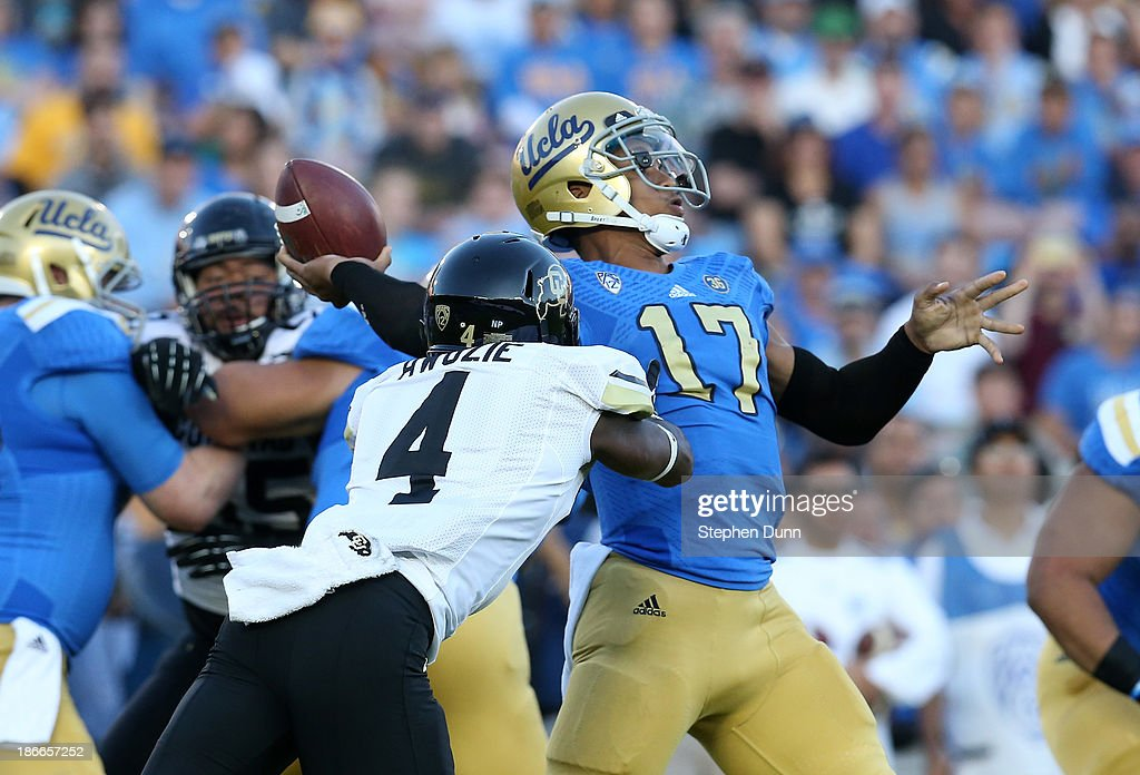 Quarterback <a gi-track='captionPersonalityLinkClicked' href=/galleries/search?phrase=Brett+Hundley&family=editorial&specificpeople=8674236 ng-click='$event.stopPropagation()'>Brett Hundley</a> #17 of the UCLA Bruins throws a 76 yard touchdown pass as cornerback Chidobe Awuzie #4 of the Colorado Buffaloes rushes in the first quarter at the Rose Bowl on November 2, 2013 in Pasadena, California.