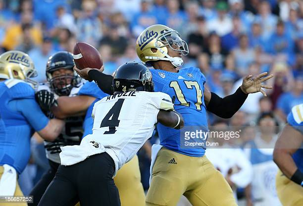 Quarterback Brett Hundley of the UCLA Bruins throws a 76 yard touchdown pass as cornerback Chidobe Awuzie of the Colorado Buffaloes rushes in the...