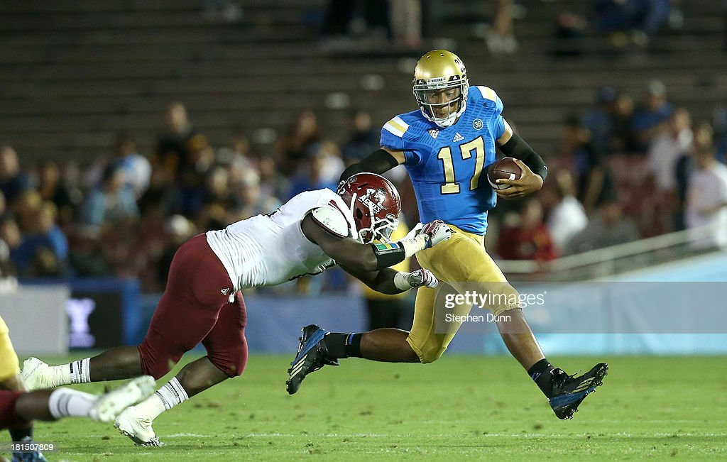 Quarterback Brett Hundley #17 the UCLA Bruins carries the ball against linebacker Trashaun Nixon #2 of the New Mexico State Aggies at the Rose Bowl on September 21, 2013 in Pasadena, California.