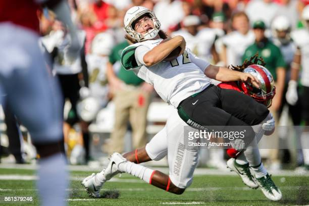 Quarterback Brooks Barden of the Charlotte 49ers is tacked by Defensive Back Drell Greene of the Western Kentucky Hilltoppers at LT Smith Stadium on...