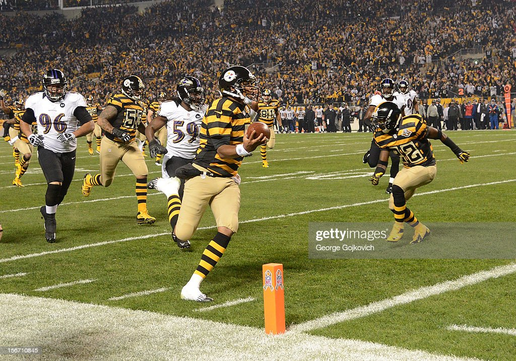 Quarterback Byron Leftwich of the Pittsburgh Steelers scores a touchdown on a 31yard run as he is pursued by defensive lineman Ma'ake Kemoeatu and...