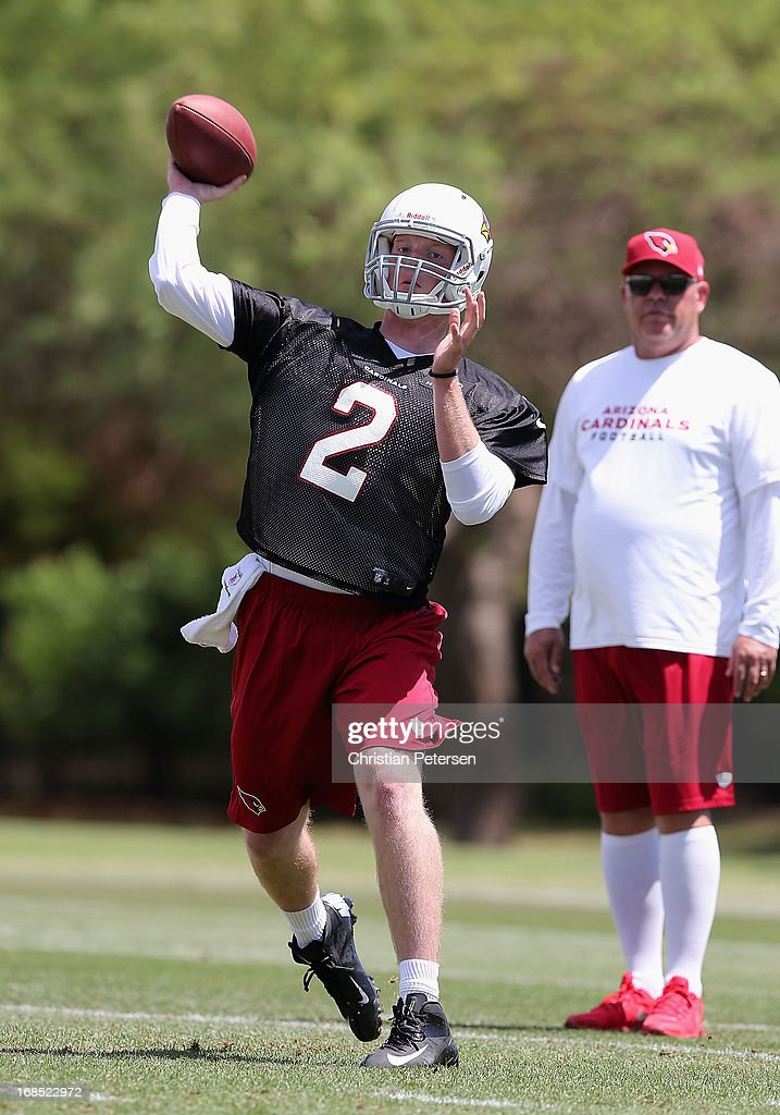 Quarterback Caleb TerBush #2 of the Arizona Cardinals throws a pass as head coach Bruce Arians looks on at the team's training center facility on May 10, 2013 in Tempe, Arizona.