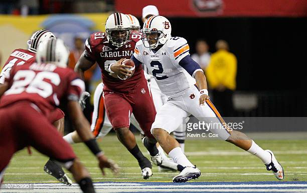 Quarterback Cam Newton of the Auburn Tigers rushes upfield against the South Carolina Gamecocks during the 2010 SEC Championship at Georgia Dome on...