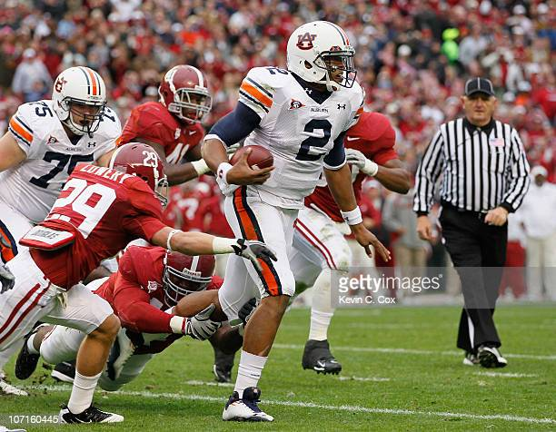 Quarterback Cam Newton of the Auburn Tigers rushes upfield away from Will Lowery and Marcell Dareus of the Alabama Crimson Tide at BryantDenny...