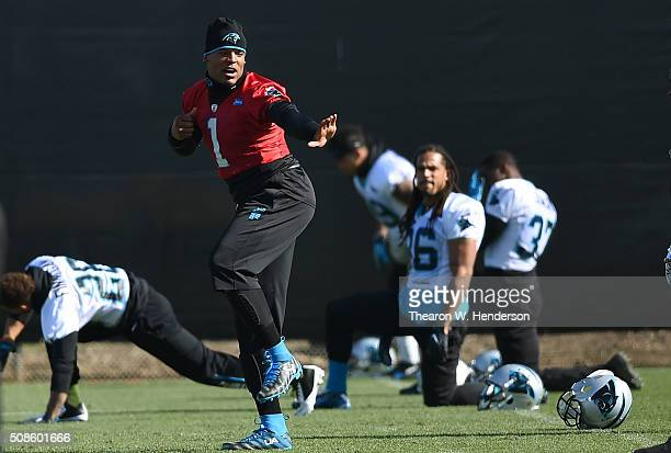 Quarterback Cam Newton of the Carolina Panthers gives the Heisman Trophy pose while his teammates stretches during practice prior to Super Bowl 50 at...