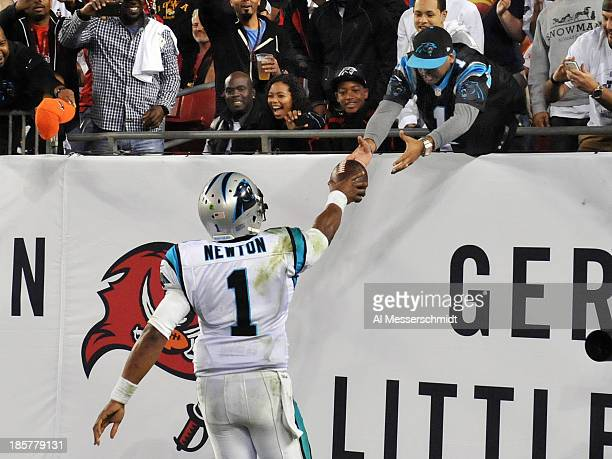 Quarterback Cam Newton of the Carolina Panthers hands a football to a fan after a touchdow against the Tampa Bay Buccaneers October 24 2013 at...