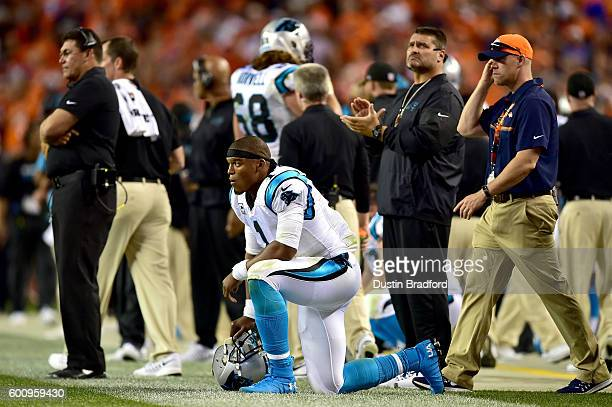 Quarterback Cam Newton of the Carolina Panthers kneels on the sideline in the fourth quarter against the Denver Broncos at Sports Authority Field at...