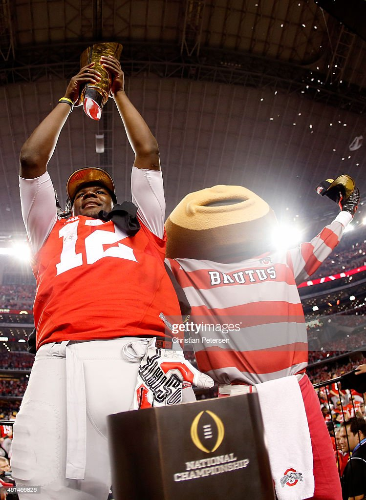 Quarterback Cardale Jones #12 of the Ohio State Buckeyes and mascot Brutus celebrate after defeating the Oregon Ducks 42 to 20 in the College Football Playoff National Championship Game at AT&T Stadium on January 12, 2015 in Arlington, Texas.