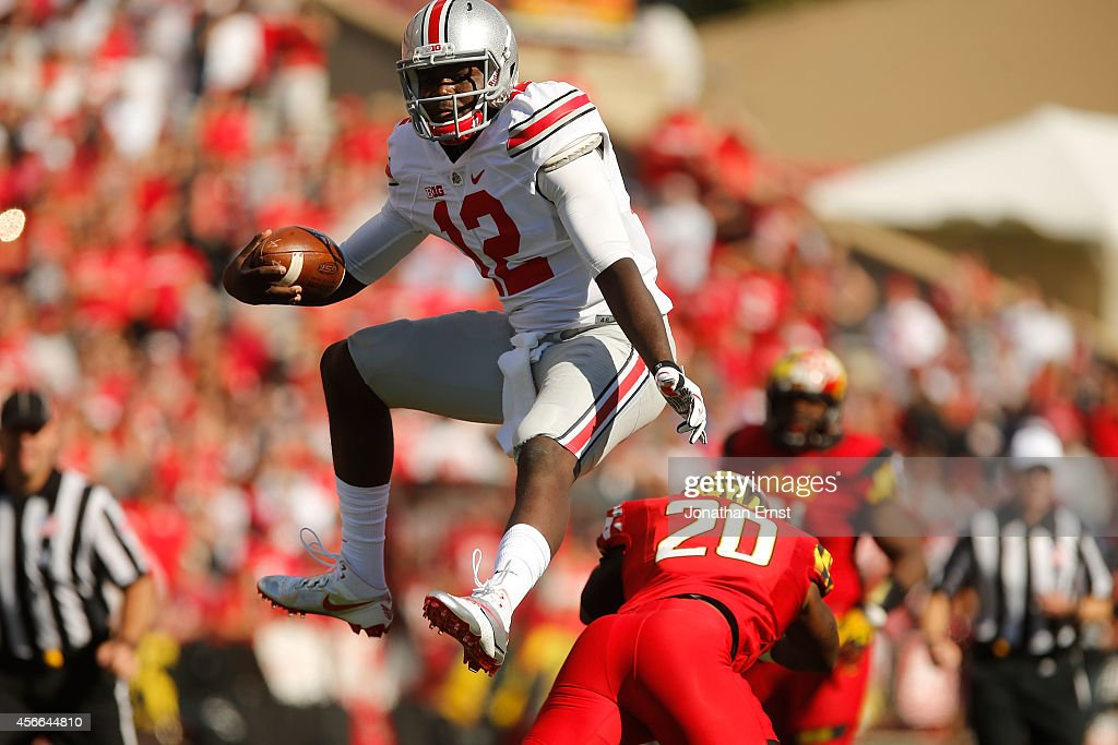 Quarterback Cardale Jones of the Ohio State Buckeyes hurdles safety Anthony Nixon of the Maryland Terrapins during the fourth quarter of Ohio State's...