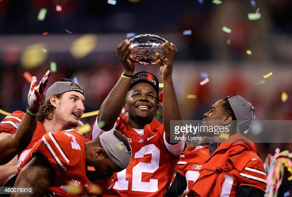 Quarterback Cardale Jones of the Ohio State Buckeyes lifts the Big Ten trophy after his team defeated the Wisconsin Badgers 590 in the Big Ten...