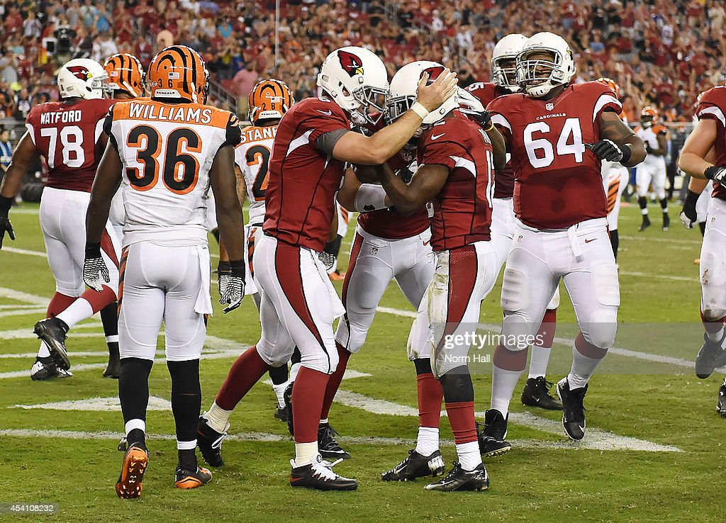 Quarterback <a gi-track='captionPersonalityLinkClicked' href=/galleries/search?phrase=Carson+Palmer&family=editorial&specificpeople=202556 ng-click='$event.stopPropagation()'>Carson Palmer</a> #3 (L) celebrates a touchdown with wide receiver John Brown #12 (C) of the Arizona Cardinals during the third quarter of the NFL Preseason game against the Cincinnati Bengals at University of Phoenix Stadium on August 24, 2014 in Glendale, Arizona.