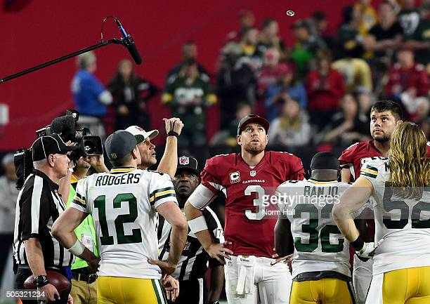 Quarterback Carson Palmer of the Arizona Cardinals and quarterback Aaron Rodgers of the Green Bay Packers watch the overtime coin toss in the NFC...