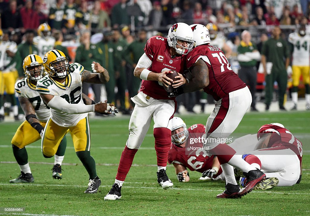 Quarterback Carson Palmer #3 of the Arizona Cardinals escapes the rush of outside linebacker Mike Neal #96 of the Green Bay Packers and throws the ball left to wide receiver Larry Fitzgerald #11 for a 75-yard gain in overtime in the NFC Divisional Playoff Game at University of Phoenix Stadium on January 16, 2016 in Glendale, Arizona.