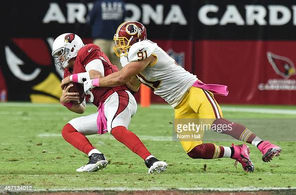 Quarterback Carson Palmer of the Arizona Cardinals is hit by linebacker Ryan Kerrigan of the Washington Redskins during the NFL game at University of...