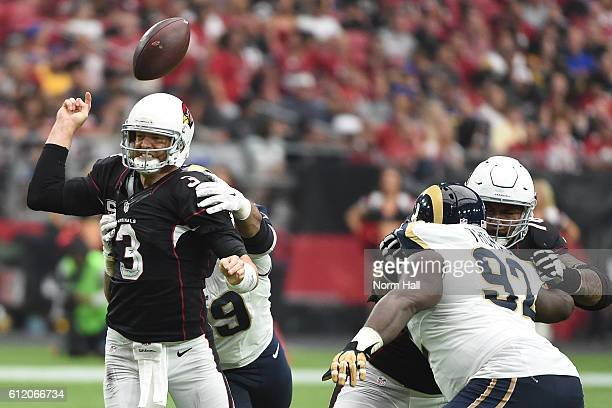 Quarterback Carson Palmer of the Arizona Cardinals is hit by defensive tackle Aaron Donald of the Los Angeles Rams during the second half of the NFL...
