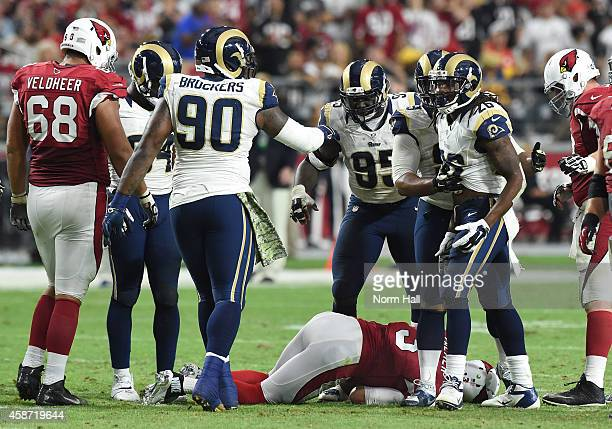 Quarterback Carson Palmer of the Arizona Cardinals lies on the ground after being injured in the third quarter of the NFL game against the St Louis...