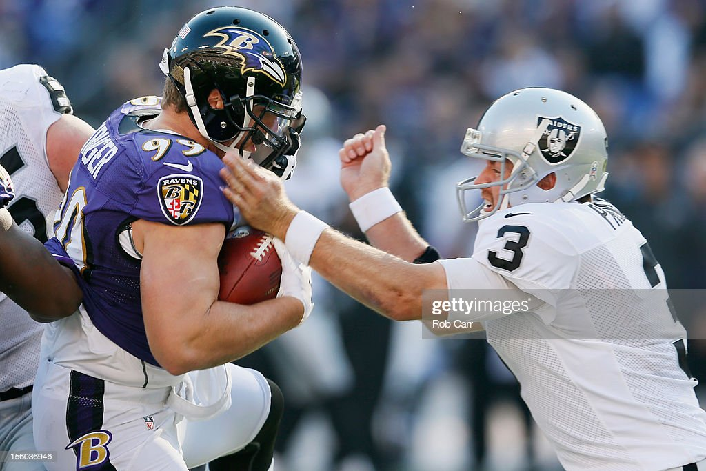 Quarterback <a gi-track='captionPersonalityLinkClicked' href=/galleries/search?phrase=Carson+Palmer&family=editorial&specificpeople=202556 ng-click='$event.stopPropagation()'>Carson Palmer</a> #3 of the Oakland Raiders tacles linebacker Paul Kruger #99 of the Baltimore Ravens after Kruger intercepted Palmer's pass during the first half of their gameat M&T Bank Stadium on November 11, 2012 in Baltimore, Maryland.