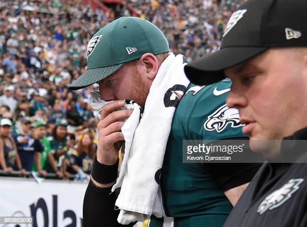 Quarterback Carson Wentz of the Philadelphia Eagles is escorted off the field after injuring his knee at the end of the third quarter during the game...