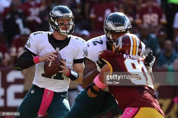 Quarterback Carson Wentz of the Philadelphia Eagles looks to pass the ball while teammate offensive tackle Halapoulivaati Vaitai blocks against...