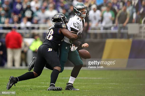 Quarterback Carson Wentz of the Philadelphia Eagles looses the ball after being hit by outside linebacker Elvis Dumervil of the Baltimore Ravens in...