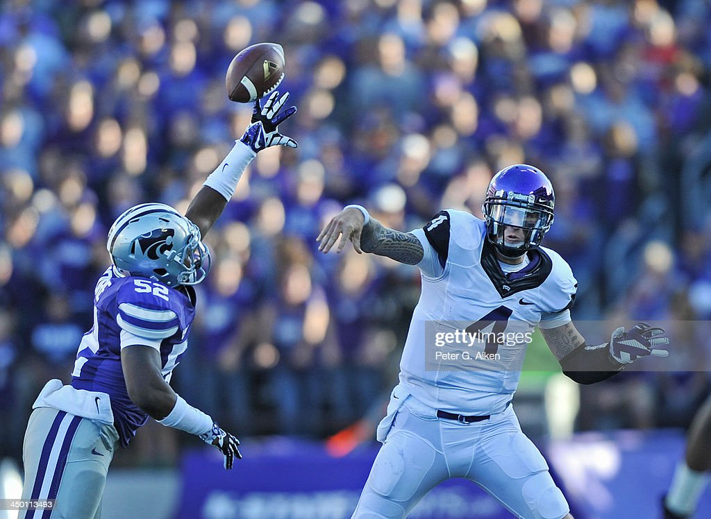 Quarterback <a gi-track='captionPersonalityLinkClicked' href=/galleries/search?phrase=Casey+Pachall&family=editorial&specificpeople=6523207 ng-click='$event.stopPropagation()'>Casey Pachall</a> #4 of the TCU Horned Frogs has his pass blocked by linebacker Charmeachelle Moore #52 of the Kansas State Wildcats during the first half on November 16, 2013 at Bill Snyder Family Stadium in Manhattan, Kansas. Kansas State defeated TCU 33-31.