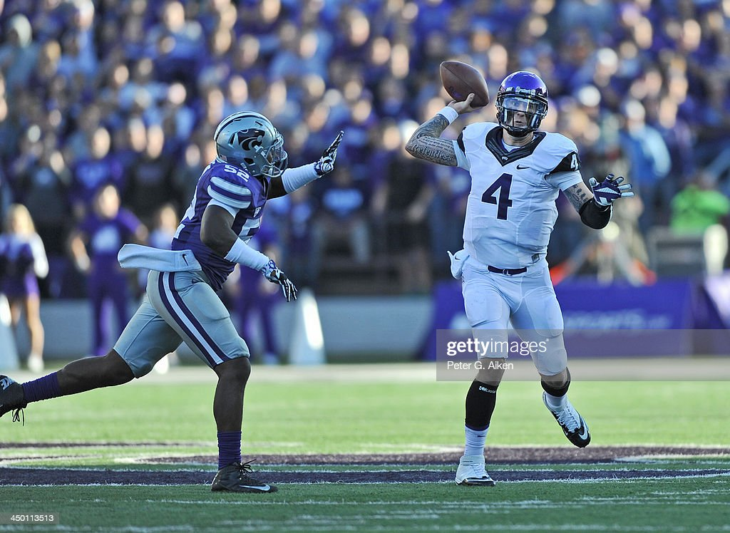 Quarterback <a gi-track='captionPersonalityLinkClicked' href=/galleries/search?phrase=Casey+Pachall&family=editorial&specificpeople=6523207 ng-click='$event.stopPropagation()'>Casey Pachall</a> #4 of the TCU Horned Frogs throws a pass down field against pressure from linebacker Charmeachelle Moore #52 of the Kansas State Wildcats during the first half on November 16, 2013 at Bill Snyder Family Stadium in Manhattan, Kansas. Kansas State defeated TCU 33-31.